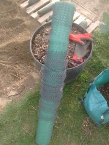 Wood chip sock mesh pulled onto filling tube
